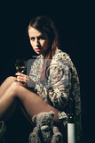 Photo studio portrait of a beautiful young brunette woman holding a bottle of white wine in retro colors