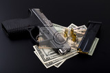 gun with bullet on us dollar banknotes crime or corruption concept on black backgroud