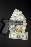 detail of gun with bullet on us dollar banknotes crime or corruption concept