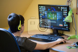 teenager using computer at home with headphones play game in his child room