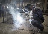 Fotografie Welder with protective mask welding reinforcement bars