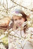 Fotografia portrait of cheerful fashionable woman in spring blooming tree with flowers in hair retro vintage color