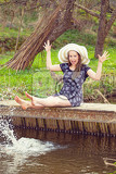 cheerful fashionable woman sits on small bridge and splashing water by her legs in warm spring day