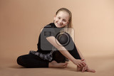 Fotografie fashion smiling european little long hair blonde girl training yoga in atelier
