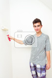 happy young teenager painting wall to white at home