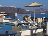 Fotografie Sea. Summer and holidays. Island, travel, shore reef pool and a parasol. Greece - Santorini.