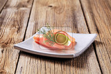 thin slice of smoked salmon and wedge of  lime
