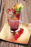 glass of iced drink garnished with fresh fruit