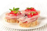 open faced ham sandwiches garnished with red pepper