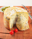 wheel of blue cheese and bowl of olives on cutting board