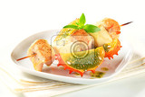 Fotografie chicken and aubergine skewer with pesto sauce and kawani fruit