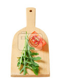 rocket leaves and tomato wedge on cutting board
