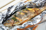 Fotografia trout stuffed with lemon and dill baked in tin foil