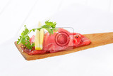 Fotografie thin slices of raw beef on wooden spatula