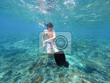 underwater shoot of a young boy snorkeling and diving in a tropical sea in nusa penida indonesia bali