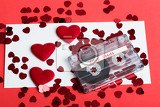audio cassette tape on red background with fabric heart valentine postcard love concept with evelope and confetti