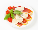 Photo sliced prosciutto crudo and mozzarella with fresh basil and tomatoes