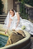Fotografie happy bride with bouquet of flower near fountain