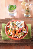 Fotografia tricolor corkscrew pasta in a terracotta bowl
