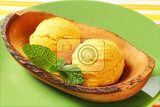two scoops of yellow icecream in olive wood bowl