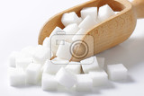 white sugar cubes in wooden scoop