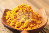 Fotografia heap of curry powder on a wooden scoop