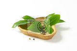 sprig of bay leaves and peppercorns in triangle wooden bowl
