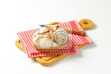crusty round loaf of bread on red checked tea towel and cutting board