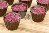 Fotografie small candy cakes from box of chocolates on wooden background