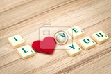 Fotografie valentines hearts on a wooden background  valentines day  day valentine postcard with scrabble text i love you