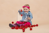 portrait of young cute baby on beige background with christmas balls