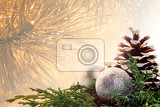 Christmas blurred background - golden shade of pine needles with water drops with Christmas decoration - silver baubles and cone on green pine needles