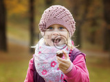 portrait little girl in autumn parkto hold in hand chestnut