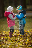 Fotografie portrait of two kids in the park as they talk together