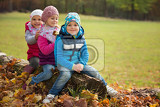 Fotografie three children sitting in a park on a tree trunk
