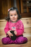 little cute curious baby girl with dark curly hair holding mobile phone