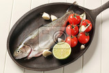 fresh trout and vegetables on cast iron pan