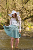 cheerful fashionable woman in stylish hat and frock posing outdoor in creek happy brunette girl with long hair in warm spring day