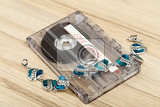 audio cassette tape with bracelet and text love songs on wooden backgound valentine postcard