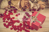 Fotografia small red hearts confetti and present box on wooden background retro color tone with drz roses