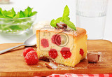 raspberry sponge cake slice on a wooden cutting board