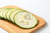 six thin slices of fresh zucchini on a wooden cutting board
