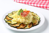 circle of thin slices of roasted zucchini with cooked potatoes fried eggs tomatoe and parsley on a white plate