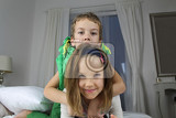 Fotografia Girl and Boy children leaned hugging each other together on bed