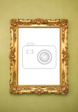 ornate picture frame hanging on a greenish wall