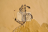 sea washing off a dollar sign drawn in the sand