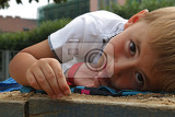 Fotografie Smiling boy is lying on sand on sandlot, playground in park and playing with grains of sand, portrait