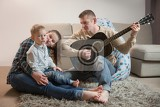 Fotografie happy family father playing guitar at home