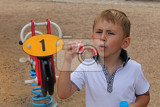 Boy, kid, child is making bubbles with bubble blower in hands on playground