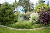 Fotografie beautiful luxury house situated in in spring garden with conifers
